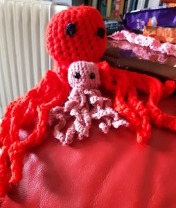 A large red crocheted octopus and a smaller pink one